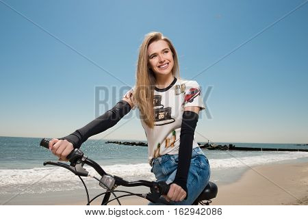 Beautiful woman ride on the beach on her bicycle at summer time