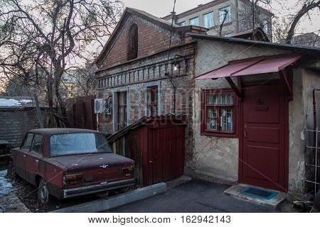 Old soviet car and small house where little man lives