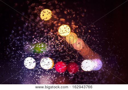 Blurred lights of heavy traffic on a wet rainy car window
