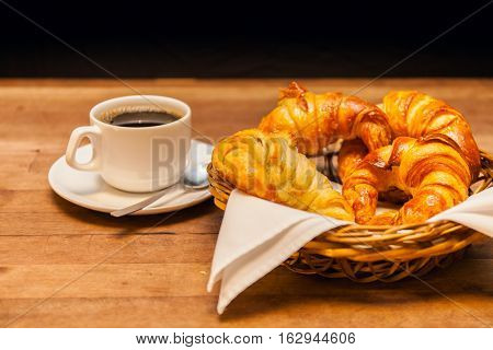 cup of coffee with croissant and a cake basket in the background. Stock image