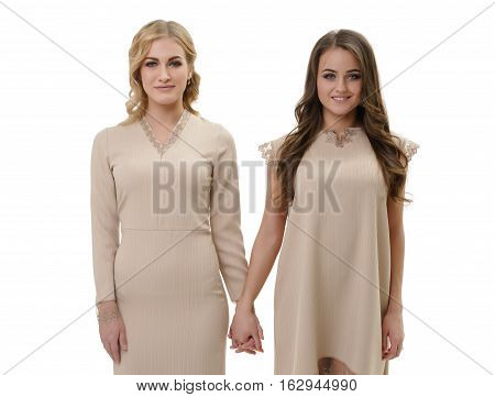 Young girls in beige dresses pose in studio staying holding hands shot from the front