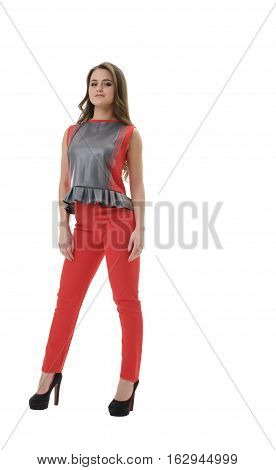 Young pretty long haired brunette in red pants, sleeveless blouse with Basques and high heels posing in studio shot from the front