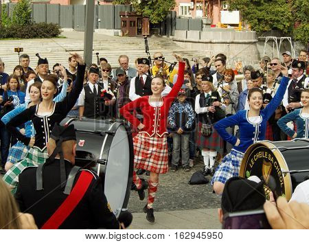 Moscow, Russia - September 4, 2016: Dancing girls during a performance of Celtic pipes and drums band surrounded by townspeople on the Crimean embankment. Festival of military orchestras