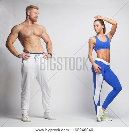 fitness man and sporty woman looking at each other isolated on studio background