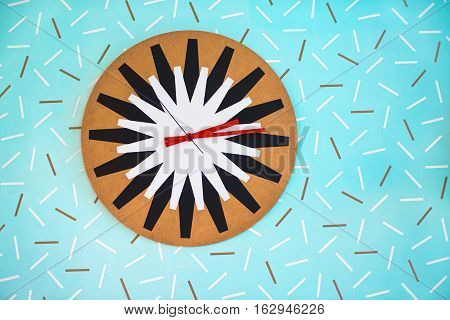Vintage colorful clock on the blue wall with pattern