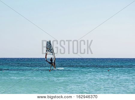 The sportsman is engaged in surfing with a sail on board.