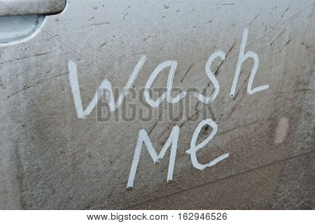 Concept photo of car wash. Inscription Wash Me on the car door dust