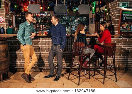 a bar, two men talking, two friends drink, two men talking near the bar