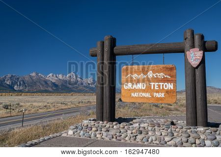 Grand Teton National Park entrance sign with mountains in the background