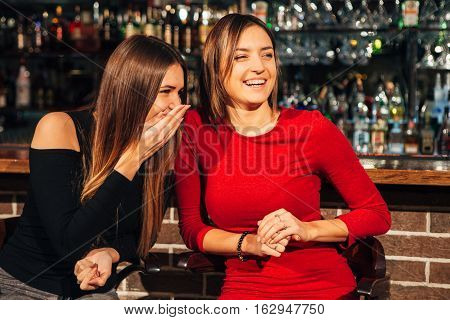 two beautiful brunette women sitting at the bar, have fun smile