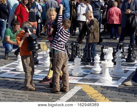 MOSCOW, RUSSIA - September 3, 2016: Pre-adolescent children on the big chess board on the city square trying to raise the figures. September 3, 2016 in Moscow, Russia
