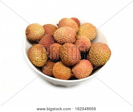 Many ripe litchi fruits isolated in white bowl top view closeup