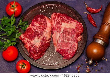 Marmara meat is tasty and healthy delicacy. Raw beef steak on a round cutting board with tomatoes, parsley and spices