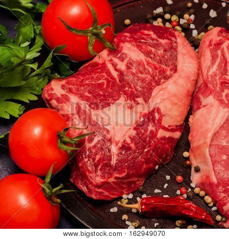 Fresh raw marbled steaks chops on black background. Marbled beef in the world recognized by the royal dish. Square black background