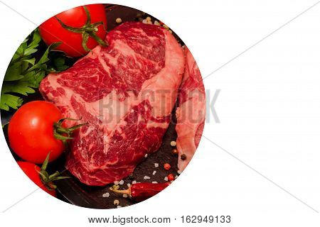 Raw Ribeye Steak with fresh herbs, tomatoes, and spices on black wood background, top view, place for text, horizontal
