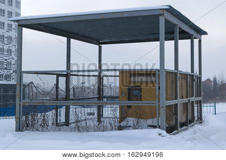 several diesel generators yellow stand under a canopy is fenced with a metal grid lying on the street white snow winter sky fog smog