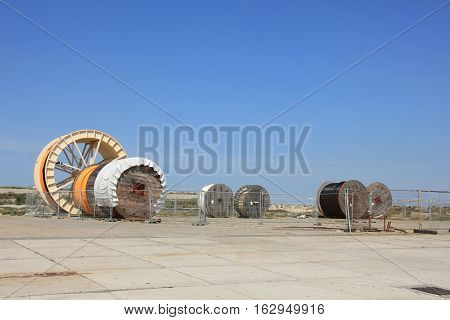 Industrial underground cables on large wooden reels different sizes