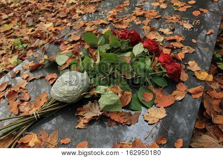 Red roses and autumn leaves on a gravestone