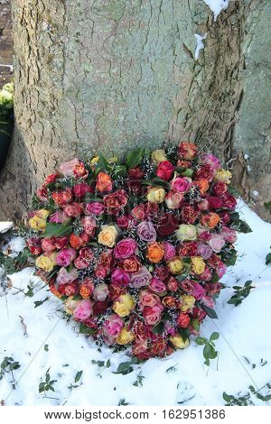 Heart shaped sympathy flowers in the snow