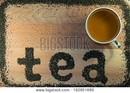 The word tea is laid out on a light-brown wooden Board small leaf black tea. Board is the background. The edges lined with a frame of tea. On Board is a mug.