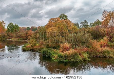 Autumn landscape with dramatic sky and clouds, colorful leaves on trees, morning at river after cold night. Autumn stream. Fall morning river. Colors of river. Nature in autumn.