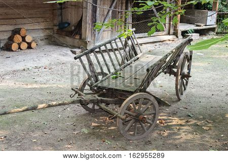 Old cart with wooden wheels in the courtyard of a peasant house