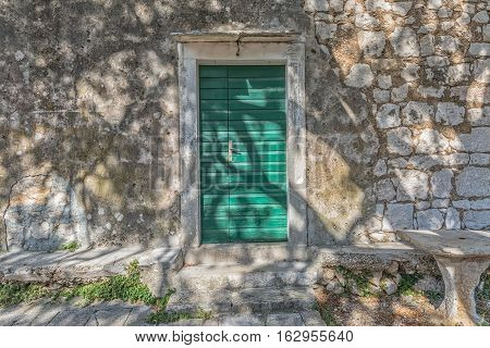 Typical house green door in Tucepi old village in the slope of a mountain Biokovo. Tree shadow texture on the facade.