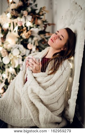Young woman relaxing with a mug of coffee as she cuddles up in warm blanket on ancient commode. Her eyes closed and serene expression.