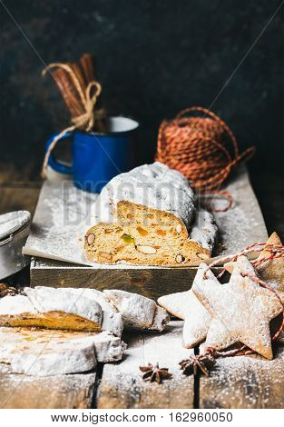 Traditional German Christmas cake Stollen with festive gingerbread cookies, selective focus, dark blue grunge background, copy space