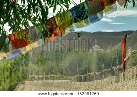Buddhist religious flags Play of light and shadow on mountains of Mulbekh Himalayan mountains with shadow of clouds in background Ladakh Jammu and Kashmir India