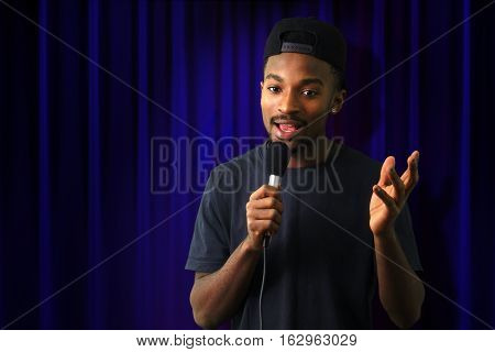young man in concert blue theater comedy vocalist singer microphone