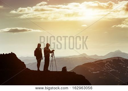 Travel concept with couple of photographers standing on mountain's top with camera and tripod and taking photo shots. Altay mountains, Siberia, Russia