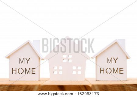 Wooden miniature house on table, on white background