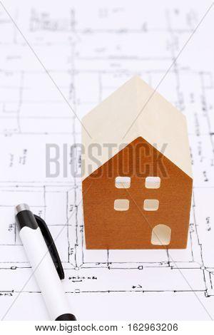 Miniature  model of house on blueprints, construction plan