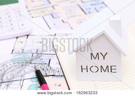 Wooden model of house and blueprints, construction plan
