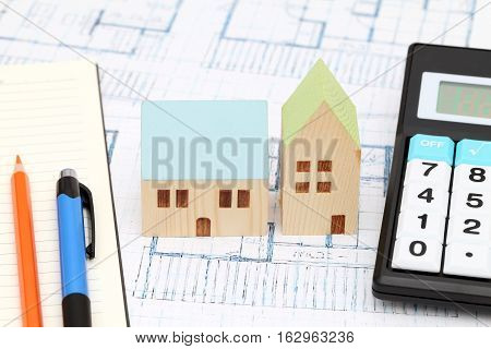 Miniature  model of house on blueprints, construction plan