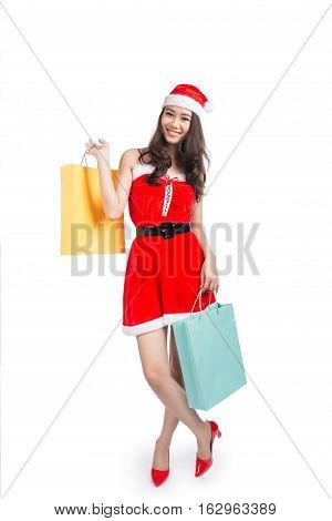 Full length portrait of a young smiling asian woman holding shopping bags before christmas