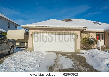 Wide garage of big luxury house with parked car and RV trailer besdie. Driveway and entrance of residential house on winter sunny day