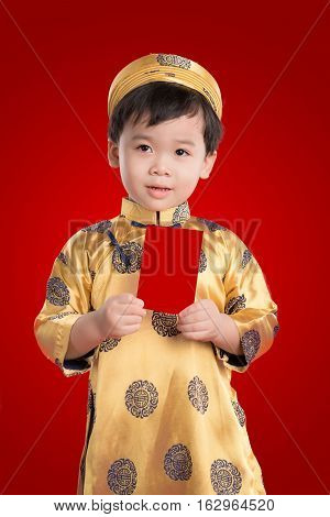 Cheerful boy wearing ao dai dress holding greeting cards for Tet holiday. It is the gift in lunar new year or Tet Holiday on red isolate background.