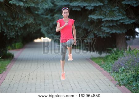 front view of a girl doing exercise outdoor in a park jogging