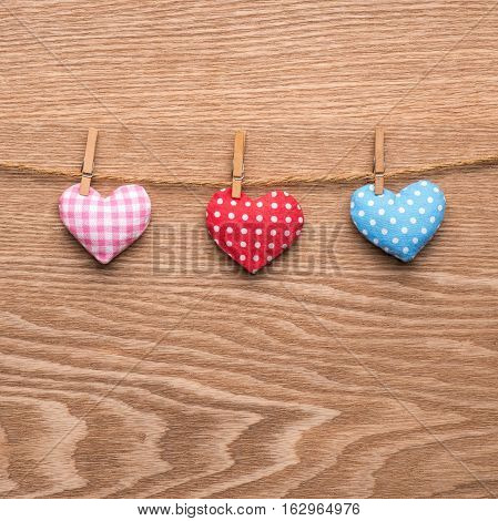Colorful heart hanging on the clothesline on wooden background.