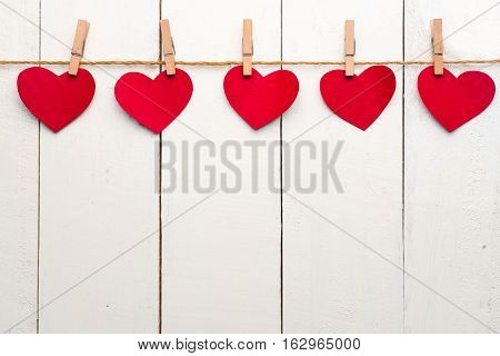 Colorful heart hanging on the clothesline on white wooden background.