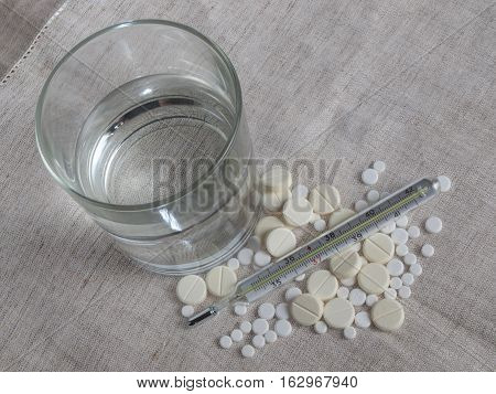 Glass of water thermometer and pills on the tablecloth top view