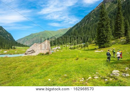 A small group of tourists in the Tien Shan mountains in summer Sunny day Kyrgyzstan.