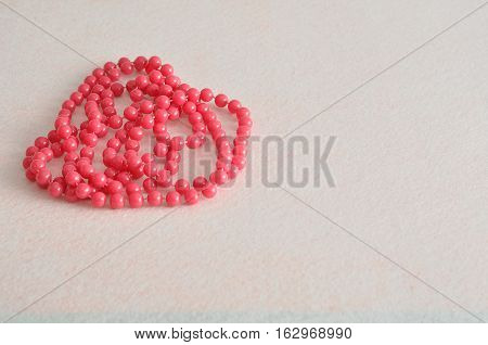 A string of pink beads necklace isolated against a white background