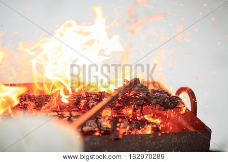 Hand with poker adjusts the coals in the brazier. Lighting the barbecue in the backyard in the winter.