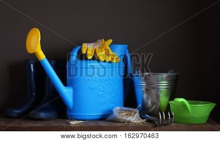 Garden tools: watering scratchy bucket rubber boots and gloves on the table. Work in the garden the beginning of the season. Still life with grain in the pack and garden equipment.