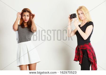 Photographer and model. Blonde girl shooting images taking photos with camera photographing mulatto female model