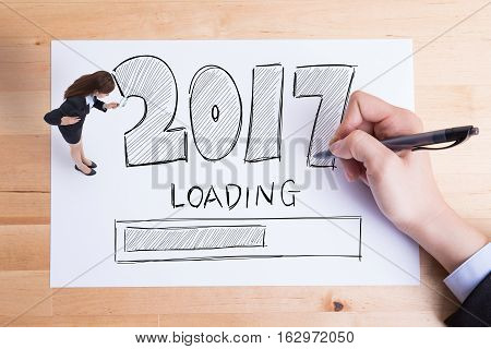 Business people writing 2017 new year loading text on the paper and woman take magnify