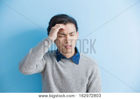 man feel headache with blue background asian